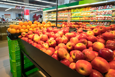 Fresh red apples on shelf in supermarket.