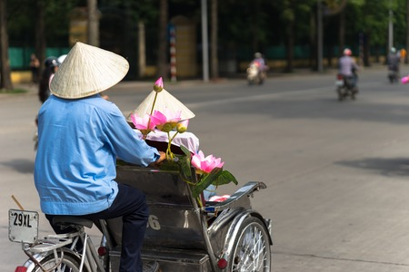 Cyclo (pedicab) driver wears conical hat on Hanoi street Imagens