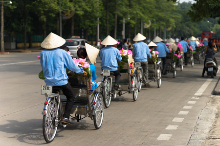 Cyclo (pedicab) driver wears conical hat on Hanoi street Stock Photo