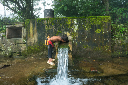 Lao Cai, Vietnam - Sep 7, 2017: Ethnic minority child drink water from small spring downstream from mountain in Y Ty, Bat Xat district Redakční