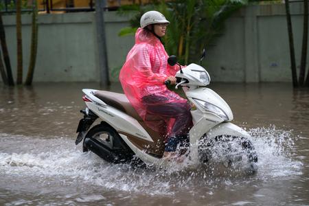 Hanoi, Vietnam - July 17, 2017: A motorcyclist rides along flooded Minh Khai street in Hanoi city, Vietnam
