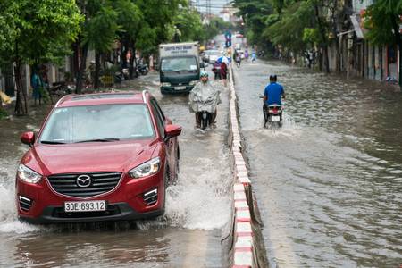 Hanoi, Vietnam - July 17, 2017: Car splashes through a large puddle on flooded street after heavy rain in Minh Khai, Hanoi.