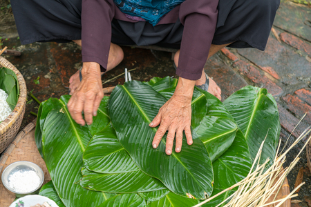 Woman hands preparing to make Chung Cake, the Vietnamese lunar new year Tet food Stock Photo