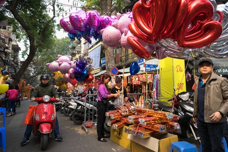 Hanoi, Vietnam - Jan 26, 2017: People take a walk buying decoration and flower for Vietnamese lunar new year on Hang Ma street Editorial
