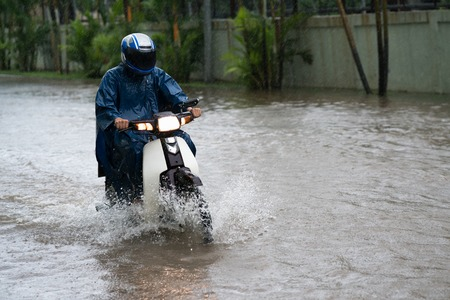 A motorcyclist rides along a flooded street in Hanoi city, Vietnam