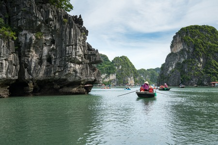 Halong bay in Vietnam, with tourist rowing boats Stock Photo