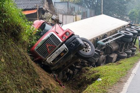 Unfall auf bergiger Straße, Kraftfahrzeugunfall, Autowrack. Langes Fahrzeug umgekippt und seitlich im Graben liegend