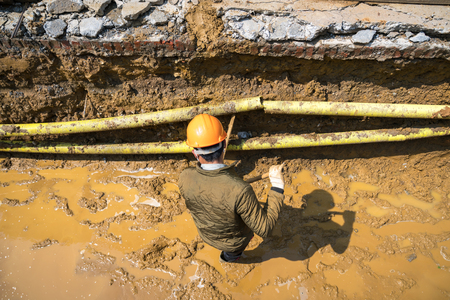 Worker working in ditch for sewage system in the city in Asia