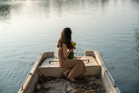 Young girl holds flowers sitting in a boat in on lake