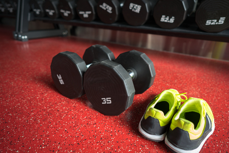Fitness dumbbells with sport shoes in gym