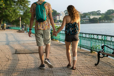 Young couple holding hands and walking through pathway on the street Banco de Imagens