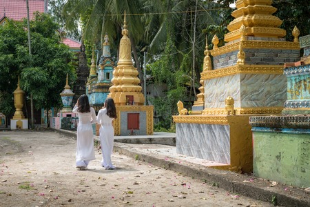 Vietnamese women in traditional dress Ao Dai walking in an ancient Buddhist temple in Southern Vietnam
