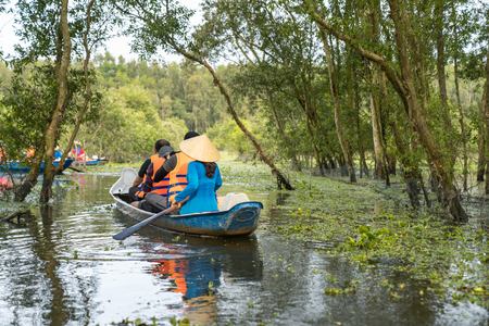 Tourism rowing boat in cajuput forest in floating water season in Mekong delta, Vietnam