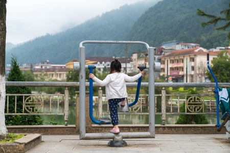 Little girl using the exercise equipment in the park to perform some workout in Sapa, Vietnam. Mountains on background
