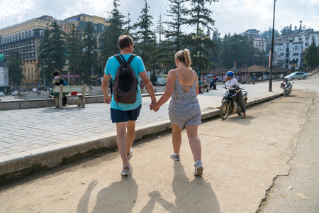 Happy couple hold hands walking in Sapa, Vietnam. Travel vacation concept