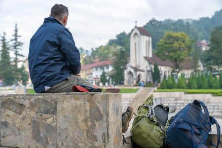 Male tourist sitting alone seeing scene in Sapa tourism town, Lao Cai, northern Vietnam