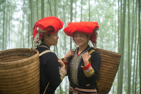 Portrait of Vietnamese ethnic minority Red Dao women in traditional dress and basket on back in misty bamboo forest in Lao Cai, Vietnam Stock fotó