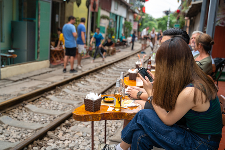 Railway cafe. People drink coffee waiting for train to arrive on railway road in Hanoi, Vietnam.