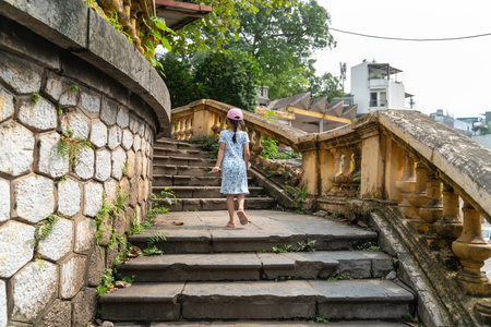 Old open outer stone staircase, aged footpath in Hanoi city with a child running up on steps Editorial