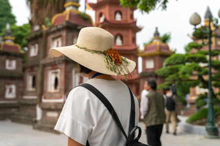 Close-up female tourist visiting Tran Quoc ancient pagoda, the oldest Buddhist temple in Hanoi, Vietnam Publikacyjne