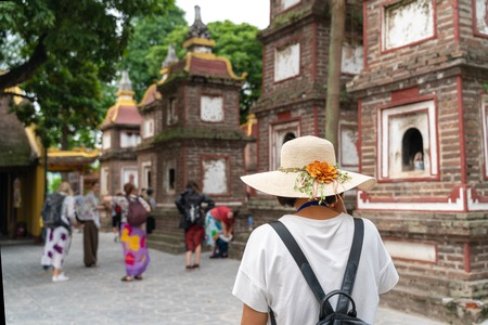 Close-up female tourist visiting Tran Quoc ancient pagoda, the oldest Buddhist temple in Hanoi, Vietnam Редакционное