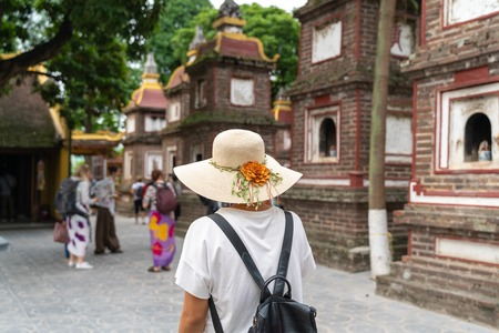 Close-up female tourist visiting Tran Quoc ancient pagoda, the oldest Buddhist temple in Hanoi, Vietnam Redakční