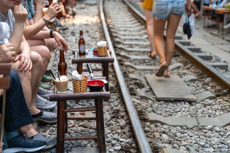 Railway cafe. People drink coffee or walking on railways waiting for train to arrive on railway road in Hanoi, Vietnam. Redactioneel
