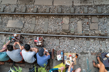 Railway cafe. People drink coffee or walking on railways waiting for train to arrive on railway road in Hanoi, Vietnam. Редакционное