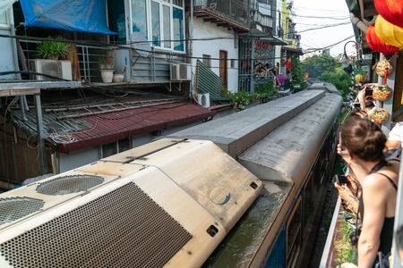 Train running on railway road with tourist watching the train from railway cafe in Hanoi, Vietnam