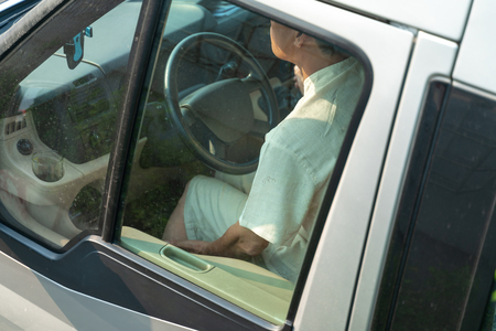 Transit car driver holding hands on steering wheel. Photo taken from outside