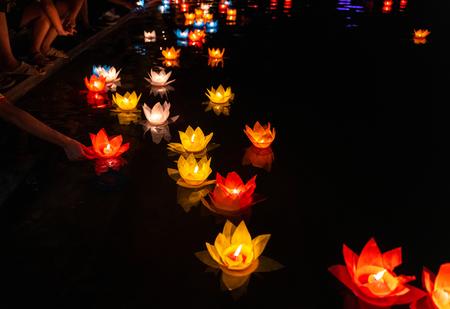 Pływające kolorowe lampiony i girlandy na rzece w nocy w dzień Vesak z okazji urodzin Buddy w kulturze Wschodu, wykonane z papieru i świecy