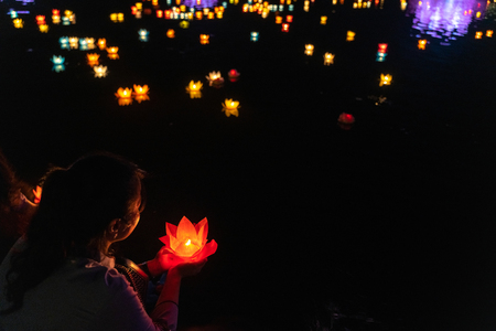 Buddhist hold lanterns and garlands praying at night on Vesak day for celebrating Buddha's birthday in Eastern culture Фото со стока