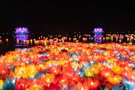 Schwimmende farbige Laternen und Girlanden auf dem Fluss in der Nacht am Vesak-Tag zum Feiern von Buddhas Geburtstag in der östlichen Kultur, die aus Papier und Kerzen hergestellt wurden