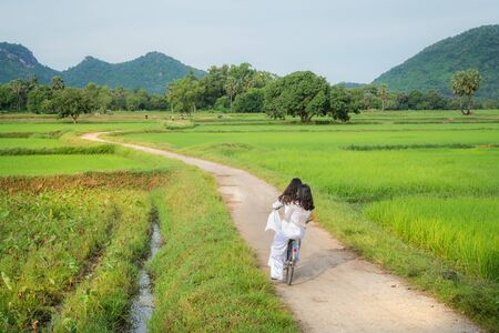 Rural landscape in Vietnam countryside with Vietnamese women wearing traditional dress Ao Dai cycling on the road