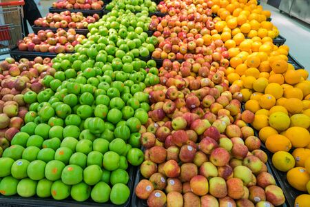 Fresh healthy fruits on shelves in supermarket