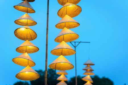 Illuminated stripe Vietnamese traditional conical hats hanging on wire for decoration, with blue sky at twilight