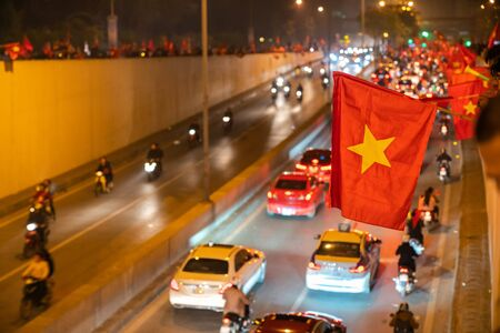 Vietnamese flags with crowd of Vietname football fans down the street to celebrate the win after soccer