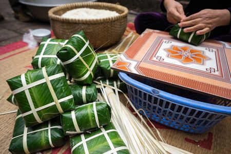 Packaged Chung cakes with female craftsman hands on background. Traditional Vietnamese New Year Tet food.