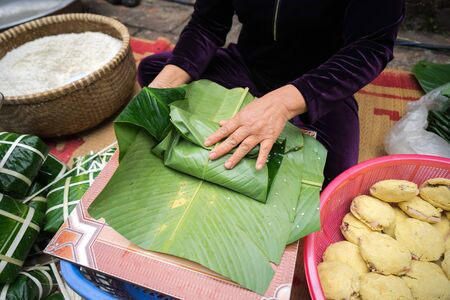 Making Chung cake by female craftsman closeup. Traditional Vietnamese New Year Tet food.