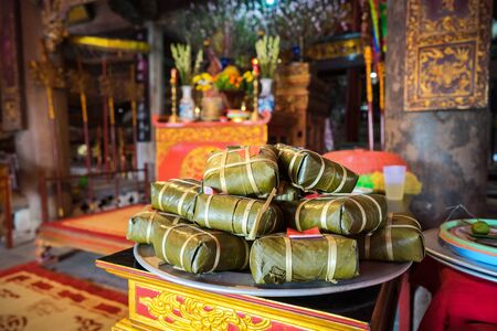 Chung cake on altar in old village communal house. Cooked square glutinous rice cake, Vietnamese lunar new year food Stock Photo
