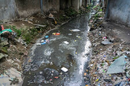 Dirty polluted waste water in big city with garbages. Environment pollution. Urban environment issues in developing countries Imagens