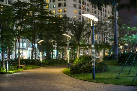 Garden walkway with lamps at night. Tree and building on background