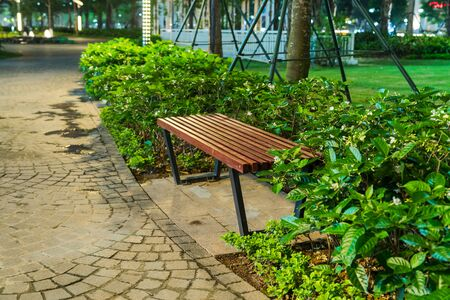 Wooden bench in the park at night with green tree surrounding
