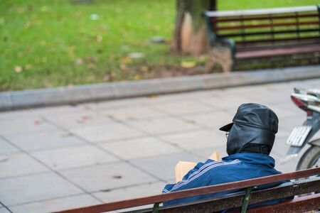 Old man with full leather hat reading book in park