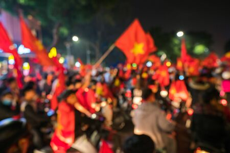 Blurred background of crowd of Vietnamese football fans down the street to celebrate the win after soccer, with a lot of Vietnamese flags raising high 版權商用圖片