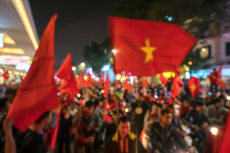 Blurred background of crowd of Vietnamese football fans down the street to celebrate the win after soccer, with a lot of Vietnamese flags raising high 版權商用圖片 - 130769392