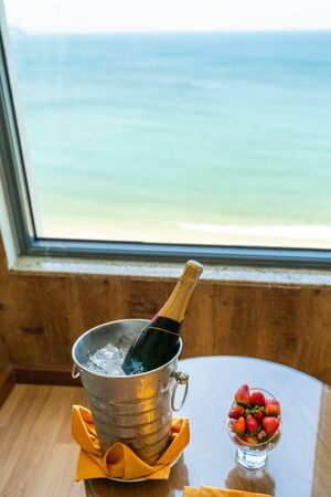 Luxury service at hotel with ocean view, expensive champagne with delicious fruits on table