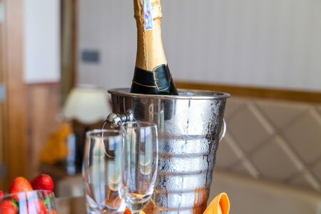 Wineglass and a bottle of chilled champagne are in an ice bucket for welcoming guests in hotel Stock Photo