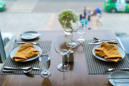 Fresh romantic breakfast table next to morning briliant light window with glasses prepare for the meal