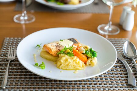 Fresh romantic breakfast table next to morning briliant light window, with salmon fish, mashed potato, vegetable, red wine